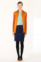 Model wears a knit cardigan w/tie, cascade front top, and straight skirt by Fiona Cibani, for the Ports 1961 Pre-Fall 2011 L'heure bleue collection, December 8, 2010.