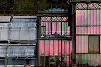 Plant History Glasshouse (formerly Australian Glasshouse) (right), 1830s, Rohault de Fleury, Jardin des Plantes, Museum National d'Histoire Naturelle, Paris, France and Incubators, (left) restored, 1995-1997, by Paul Chemetov and Borja Huidobro. Low angle view  showing the linked glass and metal structures reflecting the winter early morning light. In the middle is the small annex building containing the passage between the Plant History Glasshouse and the Incubators.