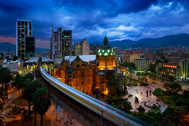 The elevated Medellin Metro is a blur as it rushes into the Parque Berrio Station in front of Plaza Botero.  The domed illuminated Palace of Culture and the art deco Museum of Antioquia frame the plaza.  The plaza is named after Medellin's native sone, and Colombia's most famous artist, Fernando Botero, who donated 23 sculptures to sit in the plaza.  A dramatic twlight sky outlines the Andes Mountains that surround the city in the Aburra Valley.