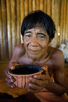 Xingu Indian senior woman holding a pot she made from clay, Amazon Basin, Brazil.