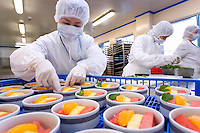 Workers add mint leaves to fruit salads in Servair center in Macau, China