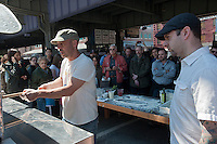 """Pizza maker and baker Jim Lahey, left,  demonstrates pizza making at the New Amsterdam Market on South Street in New York during the market's opening day for the season, Sunday, April 29, 2012. The market, located in the former Fulton Fish Market, features vendors who source their artisanal food directly from local farmers and stands of the farmers'  themselves . For opening day they promoted their """"Bread Pavilion"""" which had booths from 16 local artisanal bakeries. (© Richard B. Levine)"""