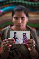 """Sharda Solanki, 36, holds up a photograph of Dr. Nayana Patel and the twins she had for an Asian client, as she sits in her house in Anand, Gujarat, India on 9th December 2012. While her husband Kantibhai works as a security guard earning 5000 rupees per month, Sharda had made hundreds of thousands with 2 surrogacies that she did with Akanksha Clinic, instantly changing her family's lives and future. """"Dr. Patel is a blessing for everyone, both parties. For us who had nothing, and others who had no children. She changed our lives."""" Photo by Suzanne Lee / Marie-Claire France"""