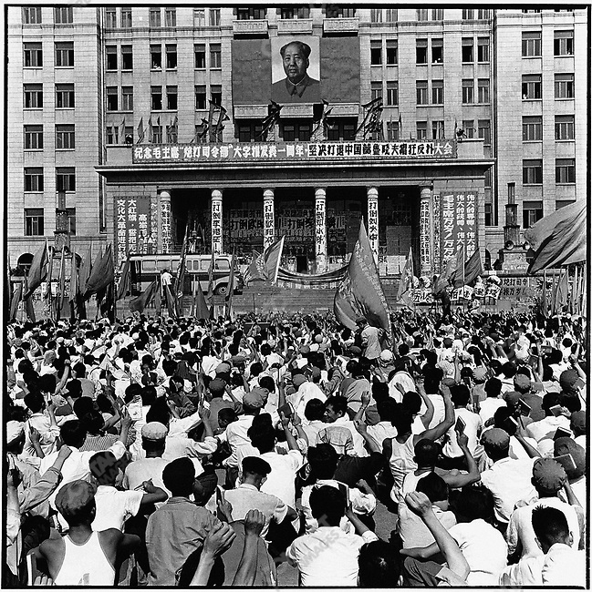 "PLA member Zhang Chunyu addresses a crowd gathered in front of the North Plaza Hotel to commemorate the one-year anniversary of Mao Zedong's ""Bombard the Headquarters"" big character poster, which precipitated the Chairman's attack on the Party establishment at the start of the Cultural Revolution. The banner reads, ""Down with Liu Shaoqi and Deng Xiaoping."" Harbin, 5 August 1967"