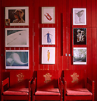 A line of red chairs designed by Lord Snowdon for Prince Charles's investiture against a red wall in the office that is decorated with artwork