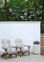The raised decking in this small garden is enclosed by a protective wall of painted clapboard