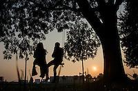 Nederland, Utrecht, 3 okt 2014<br /> Jong stel op een brede schommel die aan een dikke tak van een grote boom hangt. Romantisch plaatje bij zonsondergang.<br /> Foto: (c) Michiel Wijnbergh