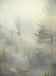 A member of the fire brigade tries to extinguish a wildfire burning in La Zoma, near Teruel, on July 23, 2009. Some 500 people were battling another wind-fuelled wildfire in northeastern Spain which claimed the lives of four firefighters and seriously injured two others. Temperatures were forecast to reach 41 degrees Celsius (105 degrees Fahrenheit) in many parts of Spain on Wednesday, raising the risk that more wildfires could break out. on July 23, 2009. (C) Pedro ARMESTRE