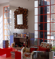 Sunlight floods in through floor-to-ceiling windows in the living room either side of the chimney breast which is decorated with mirrored mosaic tiles
