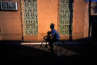 2000.03.16 Silhuetten av en mann på sykkel med sønnen sin på stanga tegnes mot en vegg. Trinidad, Cuba. © Fredrik Naumann / Samfoto   <1000056444 : DIAS : N : 412....... : SYKKEL>  27,7 MB TIF 05.05.00 12:48