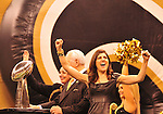 """Owner/Executive Vice President Rita Benson LeBlanc cheers, while her grandfather and owner Tom Benson has his hand on the Lombardi Trophy, as the World Champioship Banner is nveiled in the New Orleans Super Dome for the first time ever Thursday Sept. 9,2010. World Champion New Orleans Saints owner Tom Benson struts on the field sporting a one of a kind hand made """"special """"pinstripe suit"""" The striping says """" New Orleans Saint World Champions"""" all over the  Black & Gold Suit!!! His wife Gayle , on his arm,had it made for him as a surpirse and he was presented it right before opening of the NFL season in New Orleans Louisiana Thurs Sept. 9,2010. The Saints beat the Minnessota Viking 14-9. Phot © Suzi Altman"""