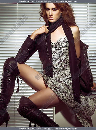 High fashion photo of a beautiful woman in leather jacket and stiletto boots sitting at a window. The photo is not model released, however the model release can be acquired from the modeling agency if necessary. Agency's fees may apply depending on the usage.