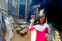 A girl smiles as she plays outside a hut in the Mirpur slum in Dhaka.