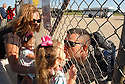 "Capt. Ben Sowders, of Lexington, kisses one of his twin daughters through the airport fence just after returning from a years tour of duty in Iraq. Sowders was met by his family at the Bowling Green Warren County Airpot. aekdb  ""Daddy's Home"""