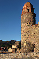 Bell tower of Eglise Notre Dame des Anges, Collioure, France, with Chateau Royal in the distance. The bell tower was converted from a medieval lighthouse and the Mediterranean Gothic style nave was built in 1684. The dome was added to the bell tower in 1810. Picasso, Matisse, Derain, Dufy, Chagall, Marquet, and many others immortalized the small Catalan harbour in their works. Picture by Manuel Cohen.