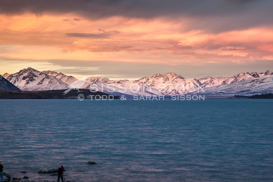 Spectacular sunset colours over Lake Tekapo and the Sib Range.  South Canterbury New Zealand. Photographer in shot.
