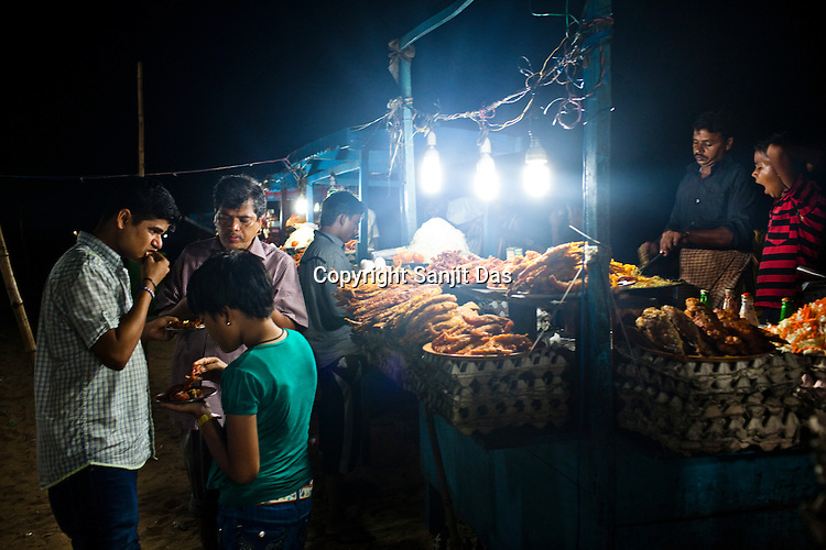 A family seen eating fried sea food on Puri Beach along the Bay of Bengal in Puri, Orissa, India. A dip in its salty waters is believed to hold great religious significance, as a result these golden sand beaches sees is a never-ending rush of pilgrims and tourists. Photo: Sanjit Das/Panos