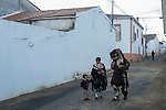 "A Carantoña (R) and his family walk in a street during the Carantoñas festival, in Acehúche near Cáceres, on January 21, 2015. The ""Carantoñas"", monster-animal characters mixing paganism with Christianity, search for Saint Sebastian in the streets of the village of Acehúche, southwestern Estremadure province, dressed in patchwork sheep, cow, rabbit and goatskins under painted masks. Arriving eventually at the village church, a procession takes place with the statue of the patron saint. Until recently, Spain's neighbors, the Berbers of Morocco, preserved a version of the same ritual in their animal-hided winter ""goblin,"" Bou Inania.  © Pedro ARMESTRE"