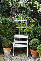 An antique garden chair backed with a wrought iron plant support fills a gap in the hedge
