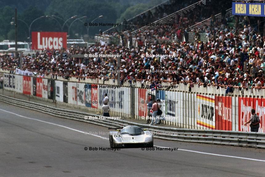 LE MANS, FRANCE - JUNE 11: The race-winning Sauber-Mercedes C9/88 88-C9-03 of Jochen Mass, Manuel Reuter and Stanley Dickens is driven past the front-straight grandstand during the 24 Hours of Le Mans at the Circuit de la Sarthe in Le Mans, France, on June 11, 1989.