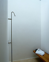 In the shower room designed in a minimalist style the plaster walls have been painted with a specialist waterproof paint