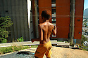 A boy in the Cantagalo favela, situated in the middle of Rio, standing on a part of a mountain, overlooking the Copacabana beach on the right, and the favela on the left. Rio de Janeiro, Brazil, 2008