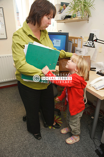 Mother in office trying to work being disturbed by daughter.