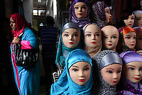 A woman walks past a selection of mannequin heads displaying hijabs in Fez, Morocco.