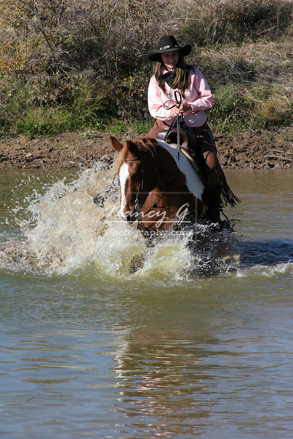 A horse and rider enjoying the water in a pond
