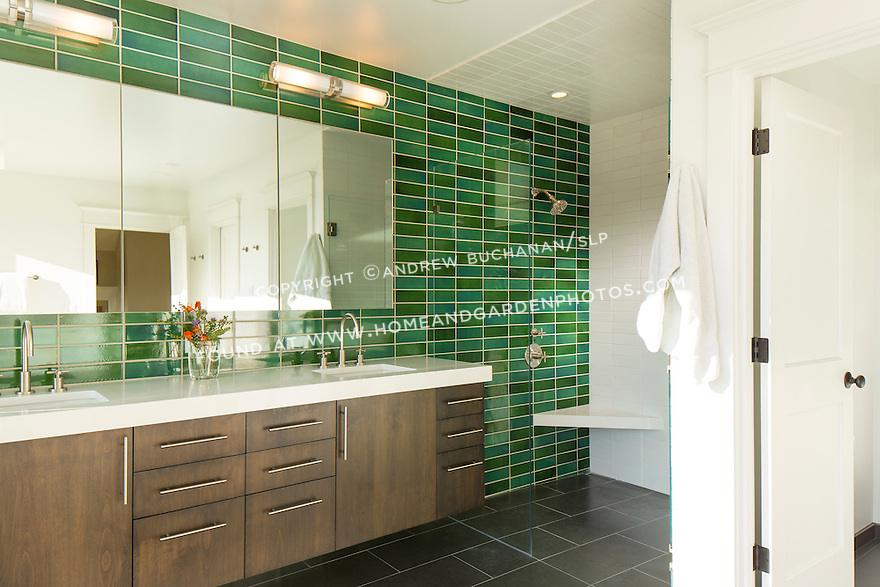 Bright green subway tiles line the wall behind a modern bathroom vanity and large shower area. This image is available through an alternate architectural stock image agency, Collinstock located here: http://www.collinstock.com