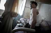 Kali, a KIA soldier lays on his bed as he recovers from a landmine explotion injury when was fighting against the Burmese army at the front line of Ntappum mountain. Fierce clashes have taken place since the ceasefire was broken out by the Burmese army last June 2011. During months the fighting were spread out along the Kachin State leaving more than 40,000 displaced persons and refugees (a conservative estimating) in accord with the humanitarian aid groups.