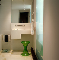 In the white-tiled bathroom of this Paris apartment a sharp accent of colour comes from the lime-green acrylic footstool