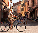 A woman wearing a leopard print dress, rides a bike down the streets of Ravenna, Italy.