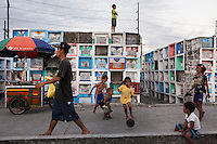 Children who live in a graveyard play and stand on the tombs in an inhabited cemetery in Paranaque City, Metro Manila, The Philippines on 18 January 2013. Photo by Suzanne Lee for Save the Children UK