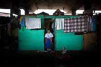 11 year old Harni Nursela, fourth grade student at Kartini Emergency School, stands in front of her makeshift home under the elevated highway near the school in North Jakarta. Originally from West Java, Nursela's parents moved to the capital in early 2007 in search of a better life, only to become scavengers collecting discarded goods and scrap metal to sell. Since the early 1990s, twin sisters Sri Rosyati (known as Rossy) and Sri Irianingsih (known as Rian) have used their family inheritance to set up and run 64 schools in different parts of Indonesia, providing primary education combined with practical skills to some of the country's most deprived children.