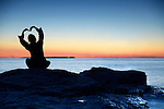 Silhouette of a woman sitting alone an a shore at sunset with her hands raise in a shape of a flower above her head, conceptual photo. Georgian Bay, Ontario, Canada.