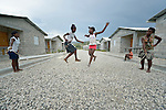 """Children jump rope in 2013 in a model resettlement village constructed by the Lutheran World Federation in Gressier, Haiti. The settlement houses 150 families who were left homeless by the 2010 earthquake, and represents an intentional effort to """"build back better,"""" creating a sustainable and democratic community. Under """"informed consent"""" rules that require prior approval, the photographer would have had to stop the girls from playing, have them identify their parents, explain the intricacies of """"informed consent"""" and usage, get their signature, and then return to the street and photograph the girls at play. That's a process that's allegedly designed to assure that the girls are not depicted in an undignified manner. Photo by Paul Jeffrey."""
