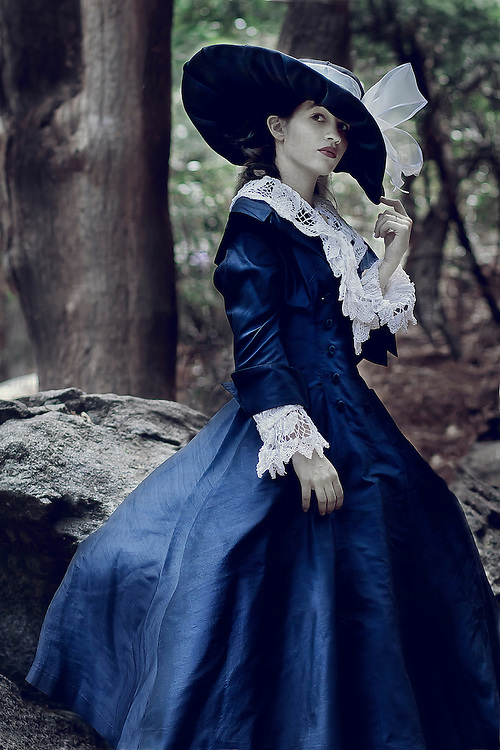 A young woman wearing vintage regency clothing and a large hat alone in woods