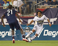 Pumas UNAM forward Martin Bravo (10) dribbles to avoid New England Revolution midfielder Shalrie Joseph (21). The New England Revolution defeated Pumas UNAM in SuperLiga group play, 1-0, at Gillette Stadium on July 14, 2010.