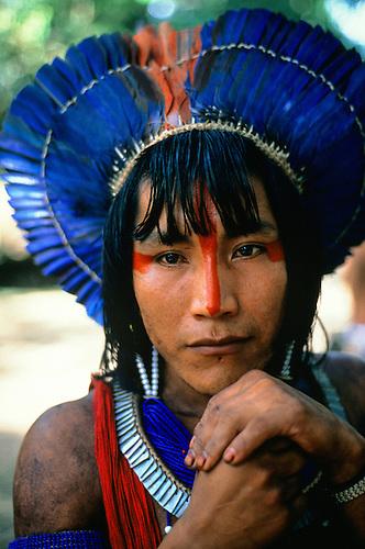 Altamira, Brazil. Ta'Kire Kayapo; warrior wearing bright blue feather headdress (cocar); Altamira Gathering, Para State, 1989.