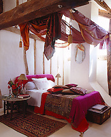 Swathes of colourful silk fabrics hang from the wooden beams above the bed in this half-timbered bedroom