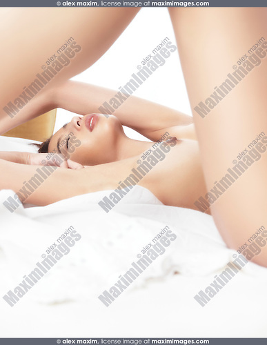 Artistic sensual closeup of a beautiful young naked woman lying in bed on white sheets