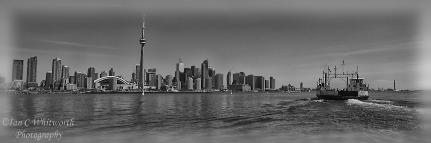 Black and white panorama of the Toronto skyline with a Toronto Island ferry in the foreground.