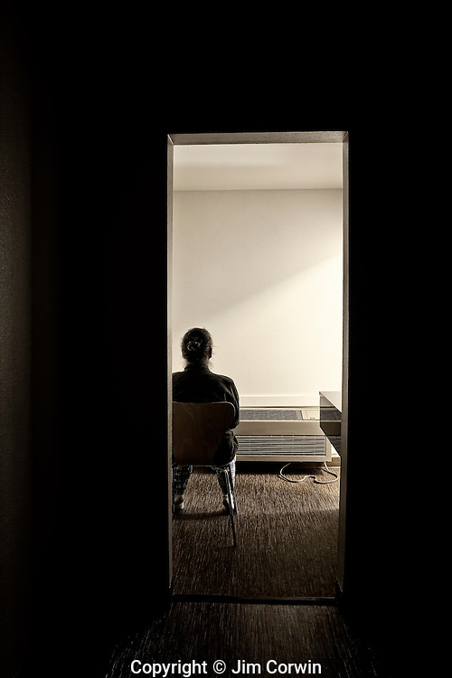 Woman sitting in chair facing wall in a sparsley furnished motel room.