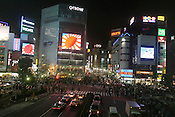 Japanese rising sun flags fly on video screens, high above the Shibuya crossing, Tokyo, Japan.