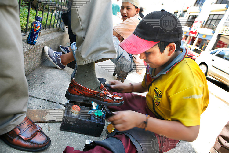 Shoe shine boys polishing the shoes of a client.