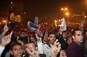 """Egyptian protesters react chant anti-Mubarak slogans and wave shoes  as a sign of both disrespect and dissatisfaction after watching a live televised speech by President Hosni Mubarak February 01, 2011 in Central Cairo's Tahrir, or """"Liberation"""" square. Mubarak announced he would not seek re-election in elections later this year and would immediately enact reforms in the constitution."""