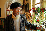 Mr. Duy Viet, a poet, orchid farmer, former mayor of Dalat, and owner of the Stop and Go cafe, lovingly caresses one of his orchids in his villa cafe. Female visitors to the cafe will receive an orchid placed behind their ear as a souvenir. All others will receive friendship.