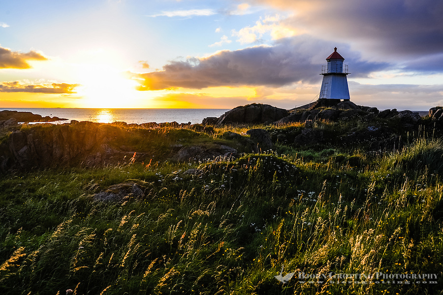 Norway, Lofoten. Hovsund on the northern part of Gimsøya. A small lighthouse at the end of the large pier. Sunset.