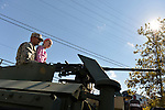 Bellmore, New York, U.S. 22nd September 2013. A young girl and Army soldier sit at the top of an armored tank at the Military Expo at the 27th Annual Bellmore Festival, featuring family fun with exhibits and attractions in a 25 square block area, with over 120,000 people expected to attend over the weekend.